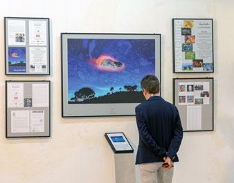 Ein Besucher betrachtet Bilder einer Fotoausstellung.