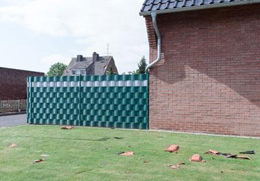 Ein Foto von herabgefallenen Dachpfannen in einem Vorgarten